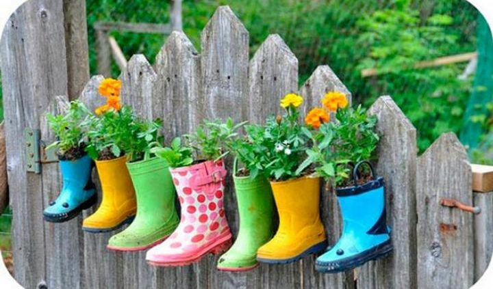 colourful rubber boots planted with flowers along a fence